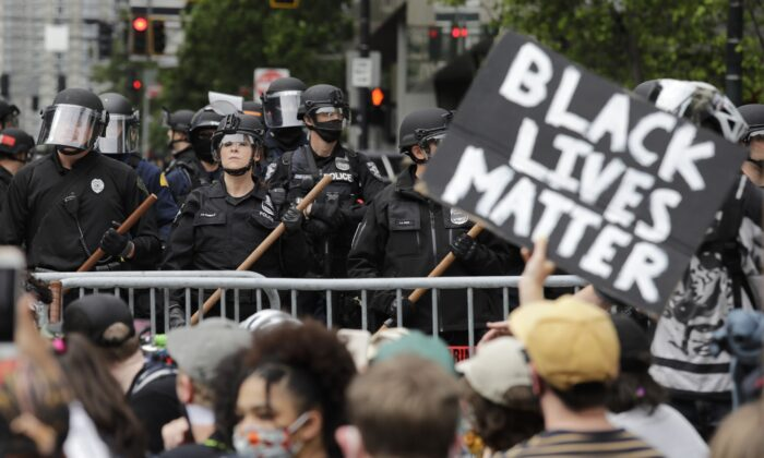In this June 3, 2020, file photo, police officers behind a barricade look on as protesters fill the street in front of Seattle City Hall, in Seattle. (Elaine Thompson/AP Photo)