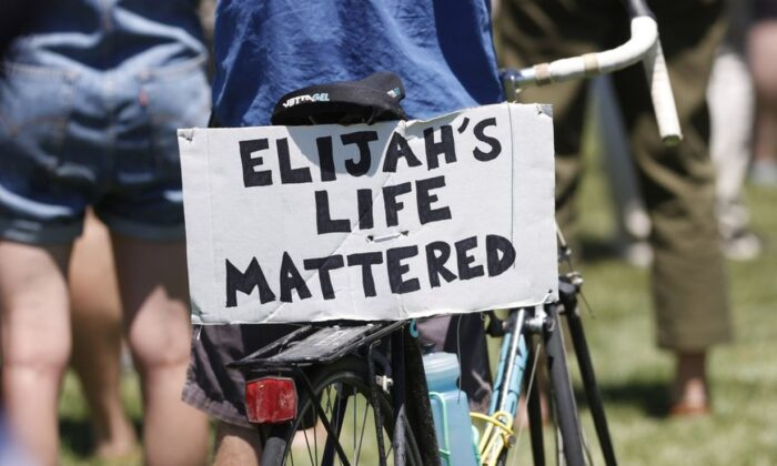 A placard is displayed on a bicycle during a rally and march over the death of 23-year-old Elijah McClain, Saturday, June 27, 2020, outside the police department in Aurora, Colo. McClain died in late August 2019, after he was stopped while walking to his apartment by three Aurora Police Department officers. (AP Photo/David Zalubowski)