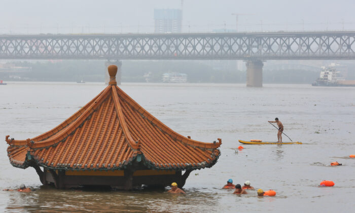 People swim near a pavilion partially submerged in floodwaters on the banks of the Yangtze River, following heavy rainfall in Wuhan, Hubei province, China July 8, 2020. (China Daily via Reuters)