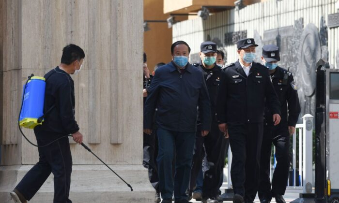 Police and officials emerge from a high school as a man (L) disinfects the entrance in Beijing on April 27, 2020. (Greg Baker/AFP via Getty Images)