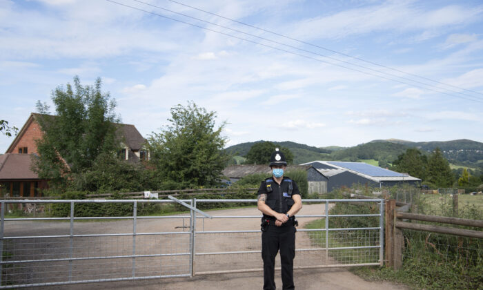 A police officer wearing a surgical face mask stands at the entrance to AS Green and Co farm in Mathon, Herefordshire, United Kingdom, on July 12, 2020. (Matthew Horwood/Getty Images)