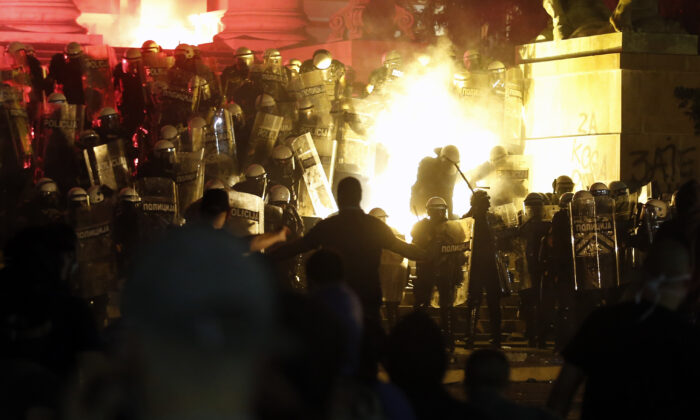 Protesters clash with riot police on the steps of the Serbian parliament during a protest in Belgrade, Serbia, on July 10 2020. (Darko Vojinovic/AP Photo)