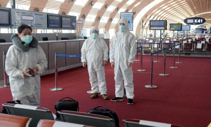 Passengers wearing protective clothing wait, prior to boarding a China Southern Airlines for Guangzhou at Charles de Gaulle Airport on the outskirts of Paris on May 12, 2020. (Eric Piermont / AFP via Getty Images)
