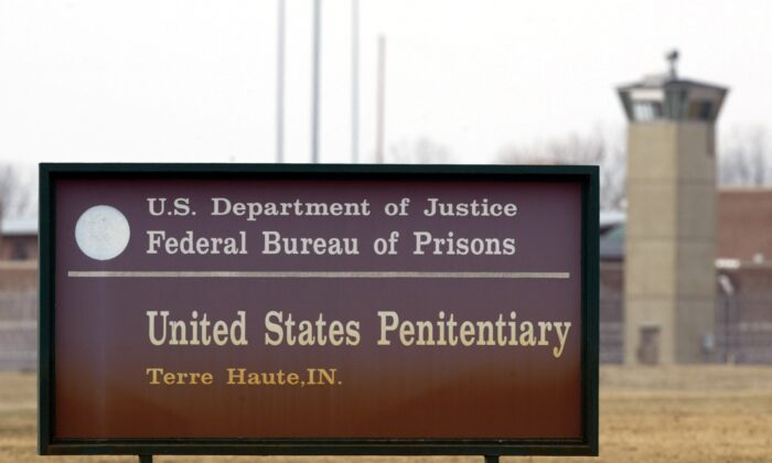 A guard tower flanks the sign at the entrance to the U.S. Penitentiary in Terre Haute, Ind., on March 17, 2003. (Michael Conroy/AP Photo)