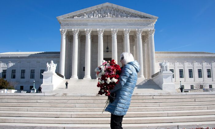 A woman helps lay 3,000 carnations to represent the approximately 3,000 abortions that occur in the United States every day, on the 46th anniversary of the Roe v Wade decision, in front of the U.S. Supreme Court in Washington on Jan. 22, 2019. (Jim Watson/AFP via Getty Images)