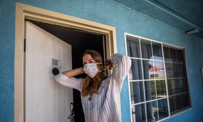 Julie Mariane puts her mask on at a motel which provided rooms to homeless people through the NGO St. Joseph Center, in Venice Beach, Calif., on April 26, 2020. (Apu Gomes/AFP via Getty Images)