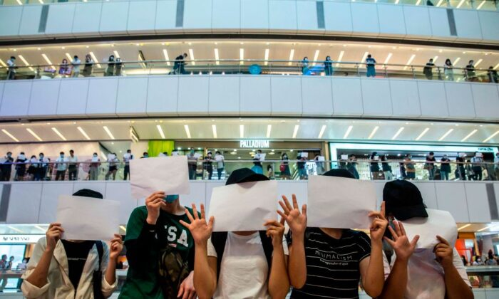 Protesters hold up blank papers during a demonstration in a mall in Hong Kong on July 6, 2020. (Isaac Lawrence/AFP via Getty Images)