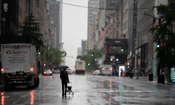 A person walks down 5th Avenue as tropical storm Fay rolls in on July 10, 2020, in New York. (David Dee Delgado/Getty Images)