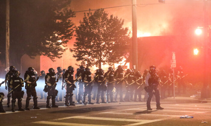 Police take back the streets at around midnight after firing copious amounts of tear gas to disperse protesters and rioters outside the Minneapolis Police 5th Precinct during the fourth night of protests and violence following the death of George Floyd, in Minneapolis, Minn., on May 29, 2020. (Charlotte Cuthbertson/The Epoch Times)