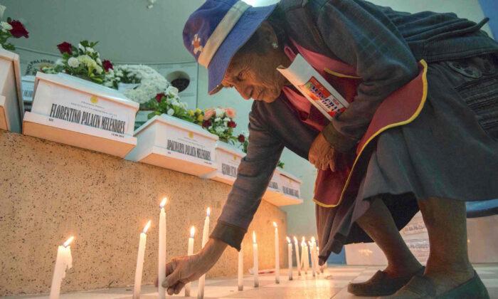 A relative lights a candle in the town of San Martin de Pangoa, Junin Department, Peru, on June 14, 2018 next to coffins containing the remains of 23 identified victims of a massacre by the Shining Path guerrillas in 1990. (CRIS BOURONCLE/AFP via Getty Images)