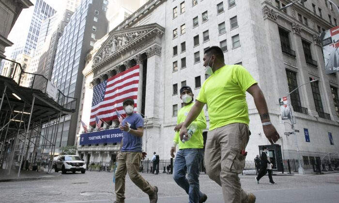 Workers wearing masks walk by the New York Stock Exchange in New York City on July 9, 2020. (Mark Lennihan/AP Photo)