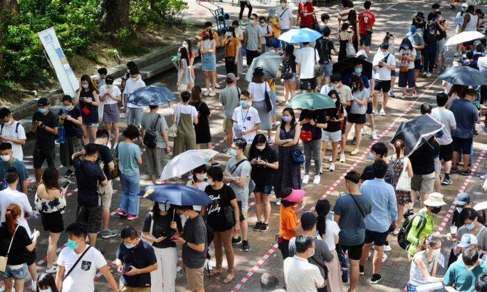 Voters queue up in long lines waiting to cast their votes in primary elections in Hong Kong, on July 12, 2020. (Song Bilung/The Epoch Times)