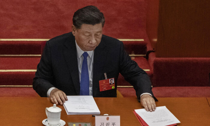 Chinese leader Xi Jinping arranges his papers at the closing session of the regime's rubber stamp legislature Congress in Beijing, China on May 28, 2020. (Kevin Frayer/Getty Images)