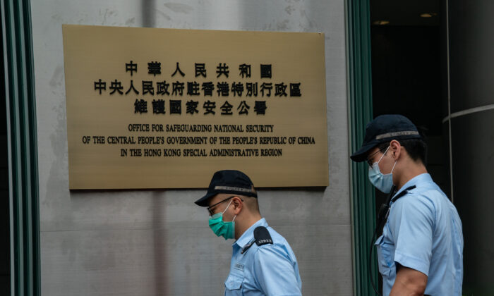Police officers walk past a plaque outside Beijing's new national security bureau office after its official inauguration in Hong Kong, on July 8, 2020. (Anthony Kwan/Getty Images)
