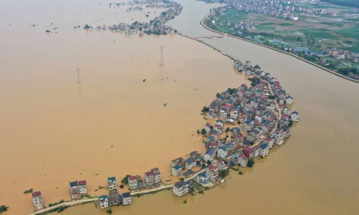 This aerial view shows submerged streets and inundated buildings after a dam was breached due to flooding in Jiujiang, China on July 13, 2020. (STR/AFP via Getty Images)