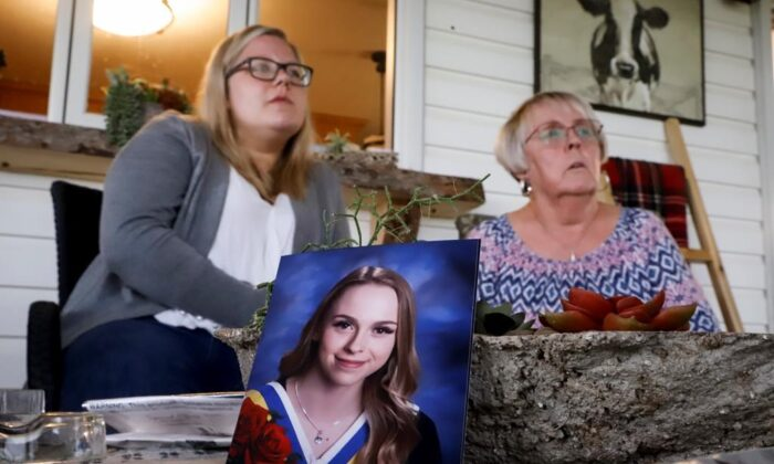 """Heather Thomson (R) and her granddaughter Jillisa Thomson speak about their experiences during the Pine Lake tornado at a 2018 graduation photo of """"miracle baby"""" Ashley Thomson at their home near Pine Lake, Alta., on July 12, 2020. (Jeff McIntosh/The Canadian Press)"""