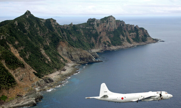 A Japanese Maritime Self-Defense Force P-3C Orion surveillance plane flies over the disputed islands, called the Senkaku in Japan and Diaoyu in China, in the East China Sea, on Oct. 13, 2011. (Kyodo News via AP/File)