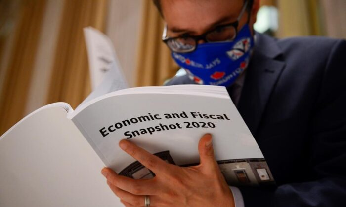 A copy of the federal government's Economic and Fiscal Snapshot 2020 is thumbed through as reporters take part in a media lock-up for the in Ottawa on July 8, 2020. (The Canadian Press/Sean Kilpatrick)