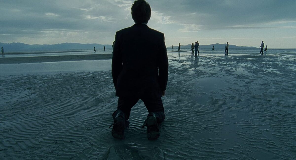 """man on knees in a suit at the beach in """"The Tree of Life"""""""