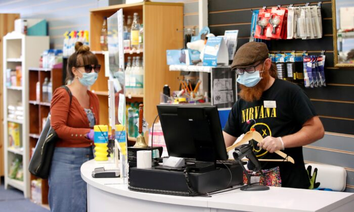 An employee wearing a protective face mask serves a customers at Willen Hospice charity shop in Milton Keynes, Britain, on June 15, 2020. (Andrew Boyers /Reuters)