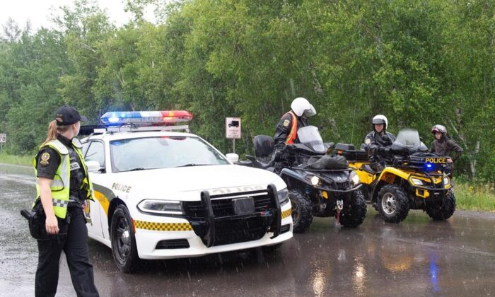 Surete du Quebec officers block the road accessing a search area near Saint-Apollinaire, Que. on July 11, 2020. (Jacques Boissinot/The Canadian Press)