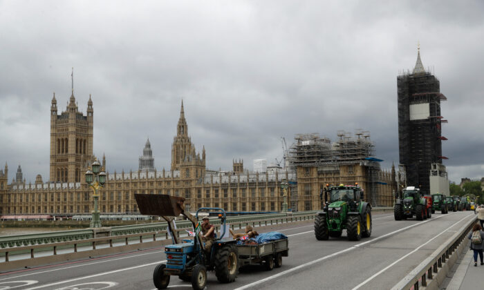 Farmers from the group Save British Farming drive tractors across Westminster Bridge, backdropped by the Houses of Parliament and the scaffolded Big Ben tower in London, in a protest against cheaply produced lower standard food being imported from the U.S. after Brexit that will undercut them on July 8, 2020. (Matt Dunham/AP)