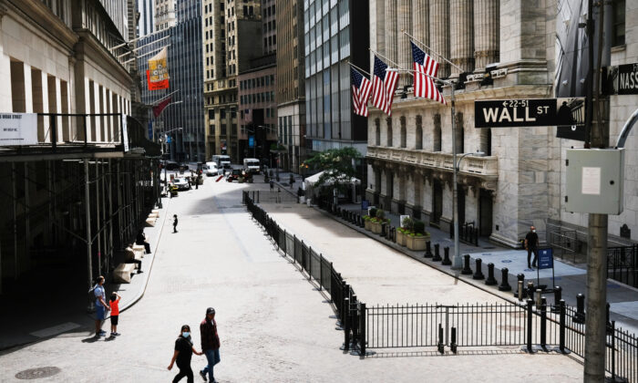 People walk by the New York Stock Exchange (NYSE) in an empty Financial District on June 15, 2020 in New York City. (Spencer Platt/Getty Images)