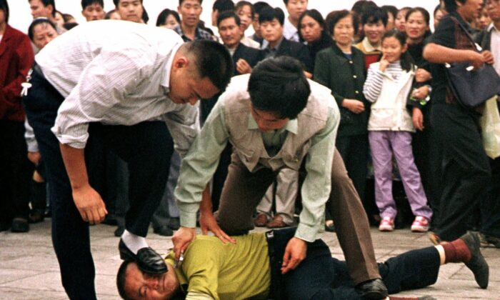 Police detain a Falun Gong protester in Tiananmen Square as a crowd watches in Beijing on Oct. 1, 2000. (AP Photo/Chien-min Chung)