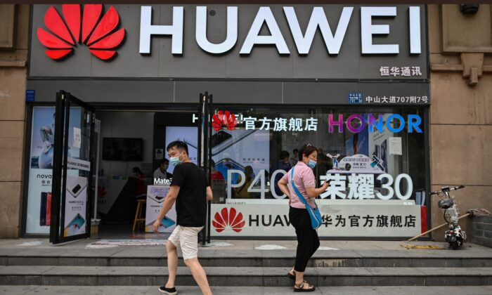 People wearing masks walk outside a Huawei store in Wuhan, Hubei Province, China, on May 26, 2020. (HECTOR RETAMAL/AFP via Getty Images)
