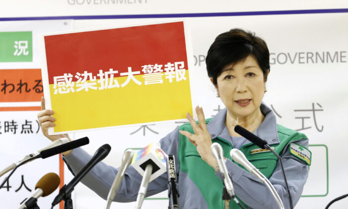 Tokyo Gov. Yuriko Koike shows a banner reading 'Infection spread alert' as she attends a news conference on the latest situation regarding the coronavirus outbreak, in Tokyo, Japan, on July 15, 2020. (Kyodo/via Reuters)
