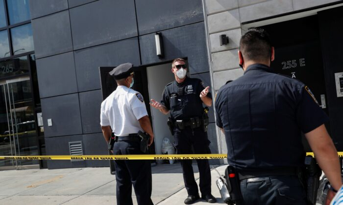 NYPD officers speak at crime scene at 265 Houston Street, where Fahim Saleh, co-founder/CEO of Gokada, was found dead at the apartment building in New York City, N.Y., on July 15, 2020. (Shannon Stapleton/Reuters)