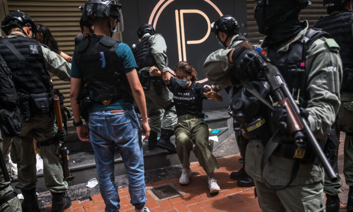 Riot police detain a woman as they clear protesters taking part in a rally against a new national security law in Hong Kong on July 1, 2020, on the 23rd anniversary of the city's handover from Britain to China. (Dale de la Rey/AFP via Getty Images)