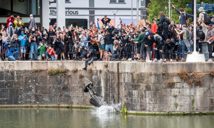 The statue of 17th century merchant Edward Colston falls into the water after protesters pulled it down during a protest following the death in Minneapolis police custody of George Floyd, in Bristol, England, on June 7, 2020. (Keir Gravil via Reuters)