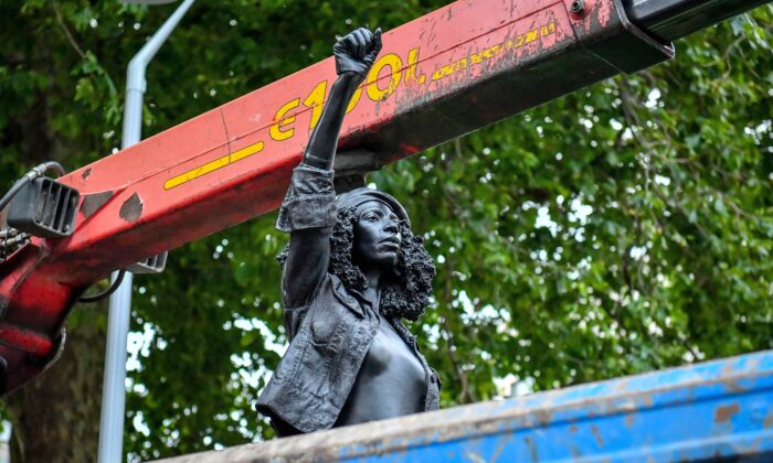 "Contractors remove the statue ""A Surge of Power (Jen Reid) 2020"" by artist Marc Quinn, which had been installed on the site of the fallen statue of the slave trader Edward Colston, in Bristol, England, on July 16, 2020. (Ben Birchall/PA via AP)"