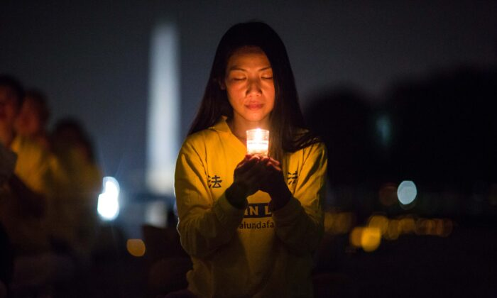 A woman joins Falun Gong practitioners hold a candlelight vigil at the Lincoln Memorial in Washington on July 20, 2017, to honor those who have died during the persecution in China that the Chinese regime started on July 20, 1999. (Benjamin Chasteen/The Epoch Times)