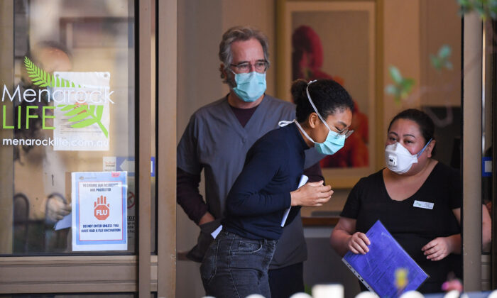 People wearing face masks are seen at the entrance of the Menarock Life aged care facility, Essendon, Melbourne, Australia on July 14, 2020, (William West/AFP via Getty Images)