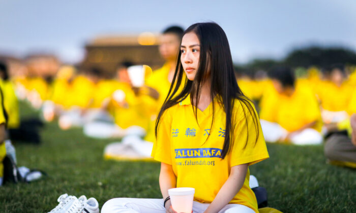 Falun Gong practitioners take part in a candlelight vigil commemorating the 20th anniversary of the persecution of Falun Gong in China on the West Lawn of Capitol Hill on July 18, 2019. (Samira Bouaou/The Epoch Times)