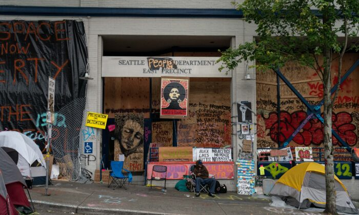 A man sits outside of the Seattle Police Department's vacated East Precinct in the area known as the Capitol Hill Organized Protest (CHOP) in Seattle on June 26, 2020. (David Ryder/Getty Images)
