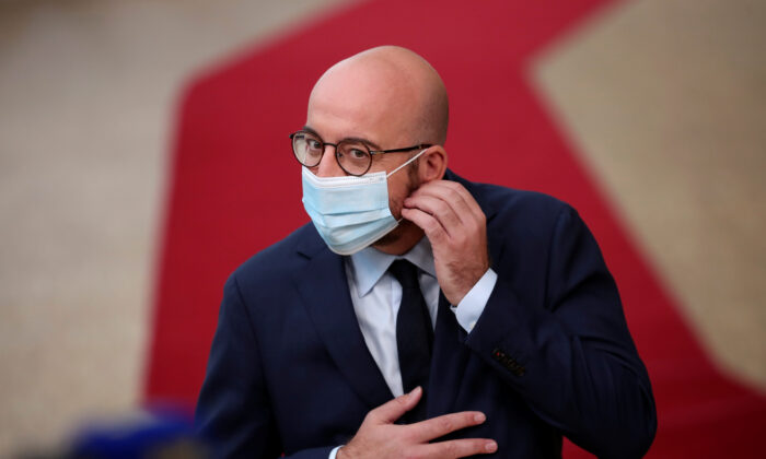 European Council President Charles Michel takes off his protective mask as he arrives for the first face-to-face EU summit since the coronavirus disease (COVID-19) outbreak, in Brussels, Belgium, on July 17, 2020. (Francisco Seco/Pool via Reuters)