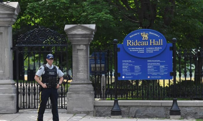 A security guard stands outside Rideau Hall where Canada's prime minister and governor general normally live. (The Canadian Press)