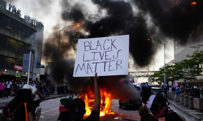 A man holds a Black Lives Matter sign as a police car burns during a protest in Atlanta, Ga., on May 29, 2020. (Elijah Nouvelage/Getty Images)