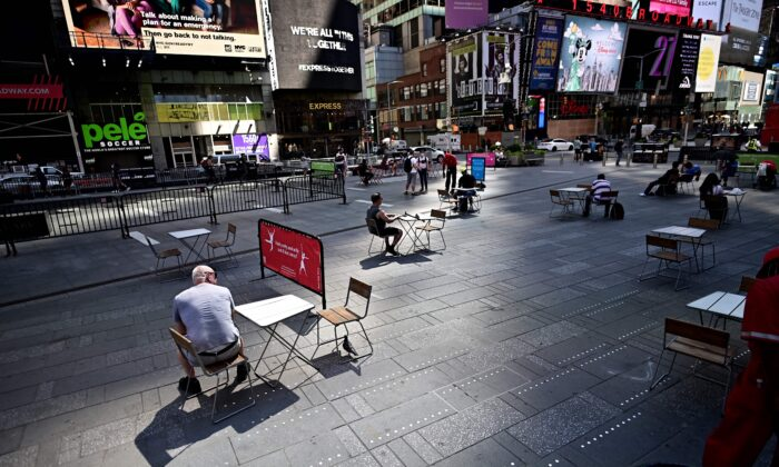 People sit on tables, respecting social distancing, at Times Square in New York City on June 22, 2020. (Johannes Eisele/AFP via Getty Images)
