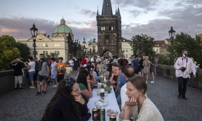 People sit at a half-kilometre long table set up on the Charles Bridge in Prague to celebrate the end of the restrictions linked to the new coronavirus pandemic on June 30, 2020. (Michal Cizek /AFP via Getty Images)