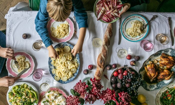 "Skye McAlpine cooks and serves ""the kind of food you can plonk down in the center of the table for everyone to tuck into, towering platefuls of it, higgledy-piggledy, unpretentious, colorful, and overflowing,"" she writes. Stars of this spread include honey-roasted poussins, spaghetti with lemon cream sauce, and burrata with preserved lemons and mint. (Photo by Skye McAlpine)"