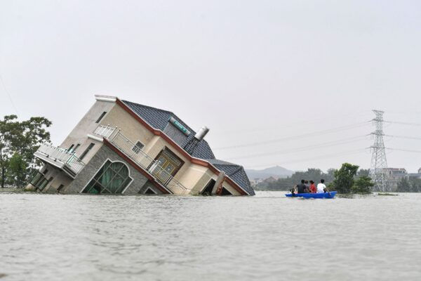 Residents ride a boat past a damaged and flood-affected house