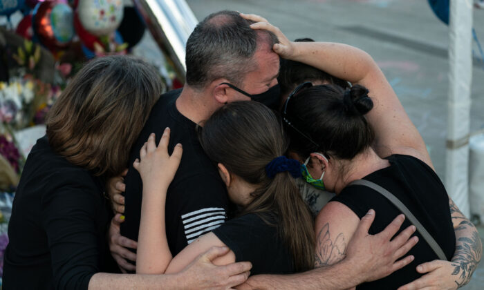 Family members embrace Police Officer Chris Rigler next to a memorial for slain officer Jonathan Shoop outside the Bothell Police Department in Bothell, Wash., on July 14, 2020. (David Ryder/Getty Images