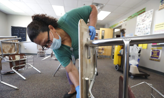 A person cleans a classroom at Wylie High School, in Wylie, Texas, on July 14, 2020. (AP Photo/LM Otero)