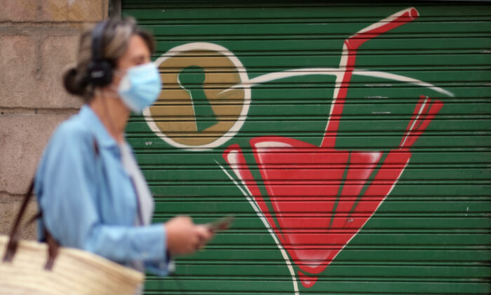 A woman wearing a face mask walks on a street, after Catalonia's regional authorities and the city council announced restrictions to contain the spread of the coronavirus disease (COVID-19) in Barcelona, Spain, on July 17, 2020. (Nacho Doce/Reuters)