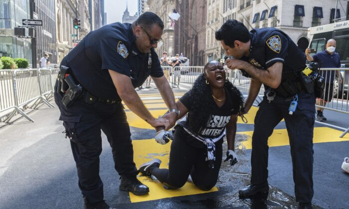New York Police Department officers attempt to detain a protester who defaced with black paint the Black Lives Matter mural outside of Trump Tower on Fifth Avenue in Manhattan on July 18, 2020. (Yuki Iwamura/AP Photo)