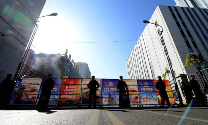 Chinese police seal off the road leading to the Urumqi Intermediate People's court in Urumqi, farwest China's Xinjiang region on September 17, 2014. (GOH CHAI HIN/AFP via Getty Images)